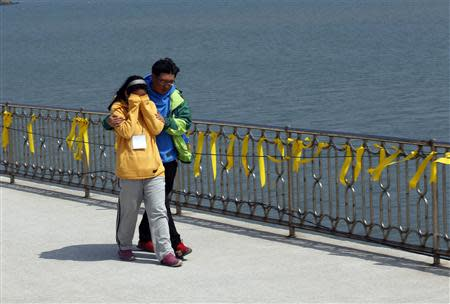 Family members of a missing passenger onboard the capsized Sewol ferry walk past yellow ribbons at a port where many family members wait for news from the search and rescue team in Jindo