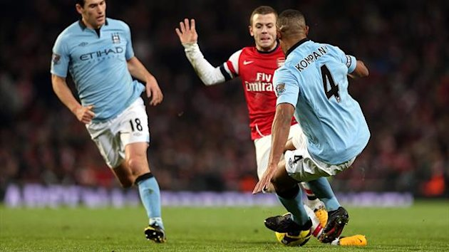 Manchester City's Vincent Kompany (front) before tackling Arsenal's Jack Wilshere (rear) for which he was issued a red card