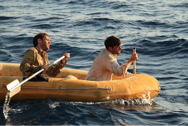 Drained and exhausted Louis (MICHAEL KOLTES) and Phil (RAY BURNS) paddling the raft. Adrift: 47 Days with Sharks