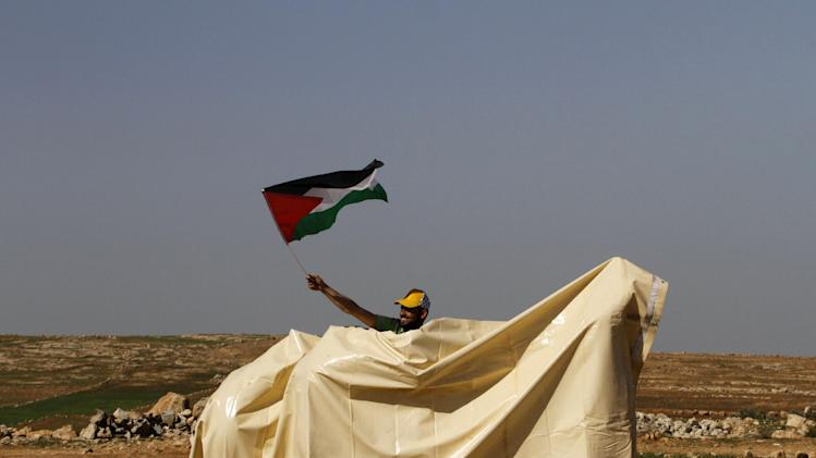 A Palestinian activist waves the Palestinian flag during a protest in Yatta, south of the West Bank city of Hebron, Saturday, Feb. 9, 2013. Palestinian activists set up a tent village to protest the settlement building in the area. (AP Photo/Nasser Shiyoukhi)