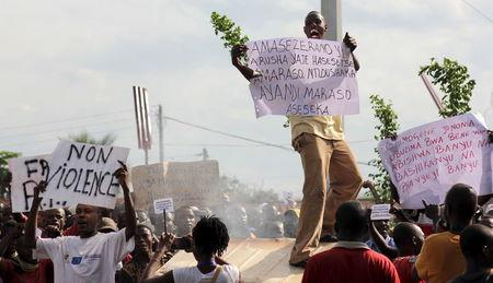 A protester carries a placard as they chant anti-government slogans during demonstrations against the ruling CNDD-FDD party's decision to allow President Pierre Nkurunziza to run for a third five-year term in office in Bujumbura, Burundi