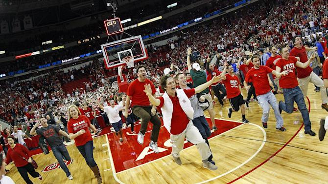 North Carolina State fans rush the court following the Wolfpack's  84-76 win over top-ranked Duke in Raleigh, N.C., Saturday, Jan. 12, 2013. (AP Photo/Karl B DeBlaker)