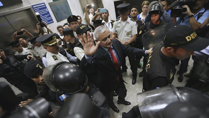 Molina gestures while being escorted by police officers after a hearing at the Supreme Court of Justice in Guatemala City