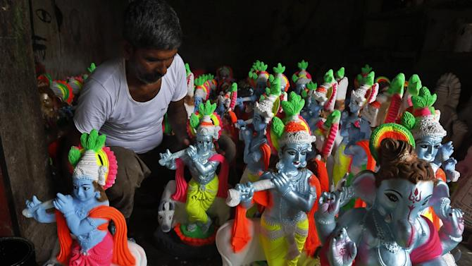 An Indian artist sits near idols of Hindu gods Krishna and of elephant headed Ganesha, foreground right as he gives them finishing touches in Allahabad, India, Monday, Aug. 11, 2014. The idols are in demand ahead of the festivals that celebrate the birthdays of these deities in the coming weeks. (AP Photo/Rajesh Kumar Singh)