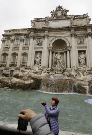 "A tourist throws a coin into Trevi's fountain, in Rome, Monday, Jan. 28, 2013. The Fendi fashion house is financing an euro 2.12 million ($2.8 million) restoration of Trevi Fountain in Rome, famed as a setting for the film ""La Dolce Vita'' and the place where dreamers leave their coins. The 20-month project on one of the city's most iconic fountains was being unveiled at a city hall press conference Monday. (AP Photo/Gregorio Borgia)"