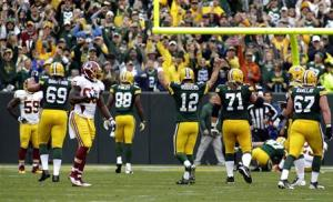 Green Bay Packers quarterback Rodgers celebrates a touch down against the Washington Redskins during the first half of their NFL football game in Green Bay