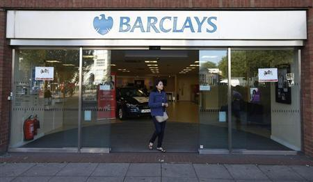 A woman leaves the Swiss Cottage branch of Barclays in London