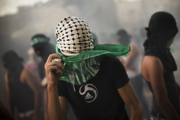 A masked Palestinian adjusts his Islamic flag during clashes with Israeli security forces, not pictured, in Shuafat refugee camp, Jerusalem, Tuesday, Sept. 18, 2012. Clashes erupted after a demonstration against an anti-Islam film called &quot;Innocence of Muslims&quot; that ridicules Islam&#39;s Prophet Muhammad. (AP Photo/Bernat Armangue)