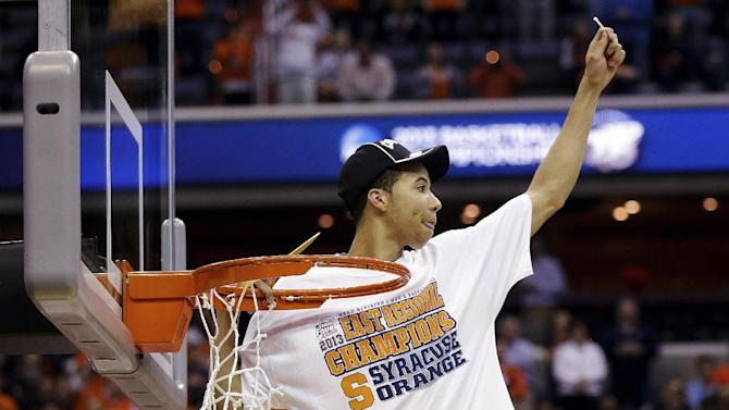 Syracuse guard Michael Carter-Williams (1) celebrates after cutting down the net following their 55-39 win over Marquette in the East Regional final in the NCAA men's college basketball tournament, Saturday, March 30, 2013, in Washington. (AP Photo/Pablo Martinez Monsivais)