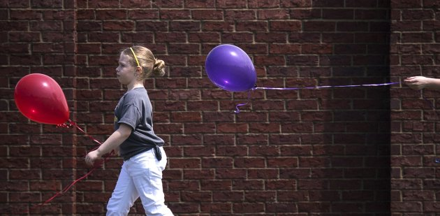 Plaza Towers Elementary School students, who survived a deadly tornado three days earlier, carry balloons home after reuniting with teachers and classmates at Eastlake Elementary in Oklahoma City