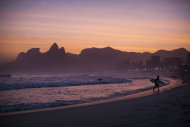 "In this Aug. 25, 2011 photo, a surfer leaves the water as the sun sets at Ipanema beach in Rio de Janeiro, Brazil. The bossa nova song, ""The Girl From Ipanema"" is turning 50, and to its legions of fans, the decades have only heightened its allure. The tune inspired by a young woman who passed the songwriters in a beach side bar on her way to the waters of Ipanema beach, carries within its chords and lyrics an image of a city that's light and easy, palm trees and blue sky, a sun-kissed life without care. (AP Photo/Felipe Dana)"