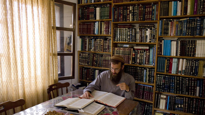 In this Aug. 31, 2011 photo, Rabbi Arele Harel studies in his home in the West Bank Jewish settlement of Shiloh, near Nablus. Harel is an Israeli rabbi setting up gay men with lesbian women in a bid to give religious homosexuals a chance to have children while remaining observant, as homosexuality is viewed as a sin and a violation of Halacha, or traditional Jewish law. (AP Photo/Ariel Schalit)