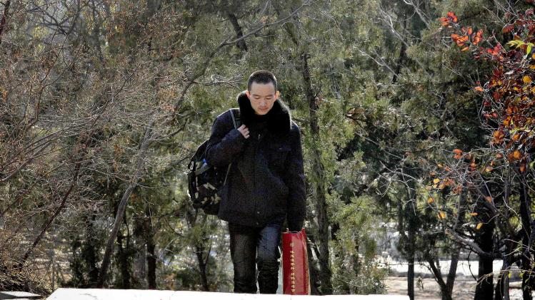 In this Nov. 20, 2012 photo, 28-year-old HIV patient Wang Pinghe walks up steps at a park after an interview in Beijing, China. Wang has a tumor in his liver and he wants it surgically removed before it becomes life-threatening, but it will be hard to find a hospital that will do the operation because he has AIDS. In China, hospitals routinely reject people with HIV for surgery out of fear of exposure to the virus or harm to their reputations (AP Photo/Gillian Wong)