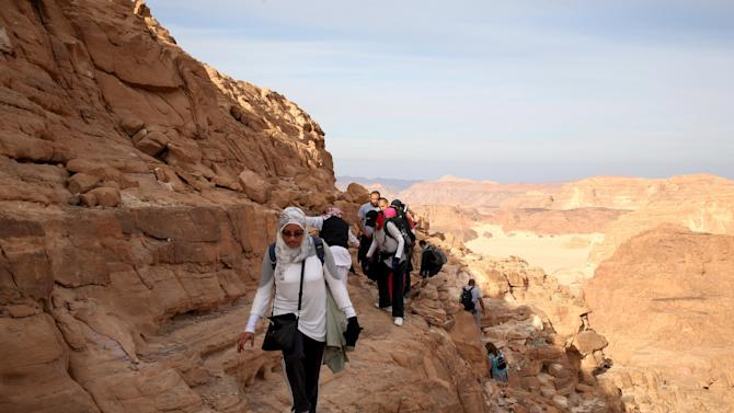 Hikers walk to reach the top of Naqba Rum area in South Sinai