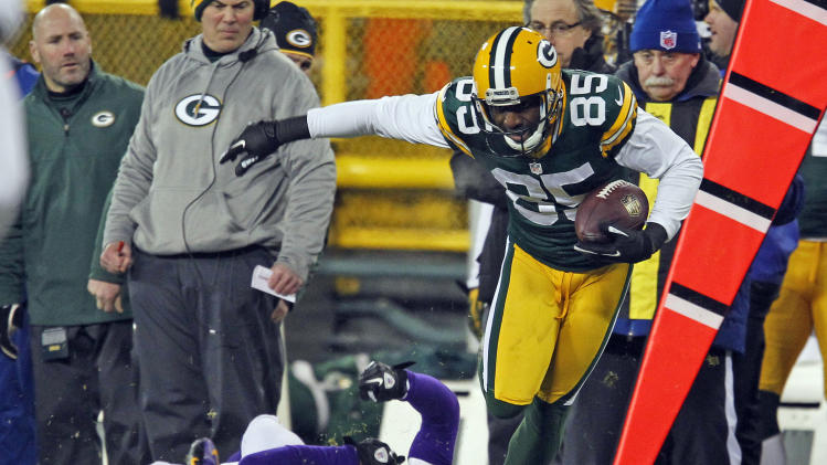 FILE - In this Jan. 5, 2013, file photo, Green Bay Packers wide receiver Greg Jennings breaks the tackle of Minnesota Vikings cornerback Chris Cook during an NFL wild card playoff football game in Green Bay, Wis. A person with knowledge of the deal tells The Associated Press that the Minnesota Vikings have agreed to terms on a deal to land free agent receiver Greg Jennings from their rivals in Green Bay. (AP Photo/Matt Ludtke, File)