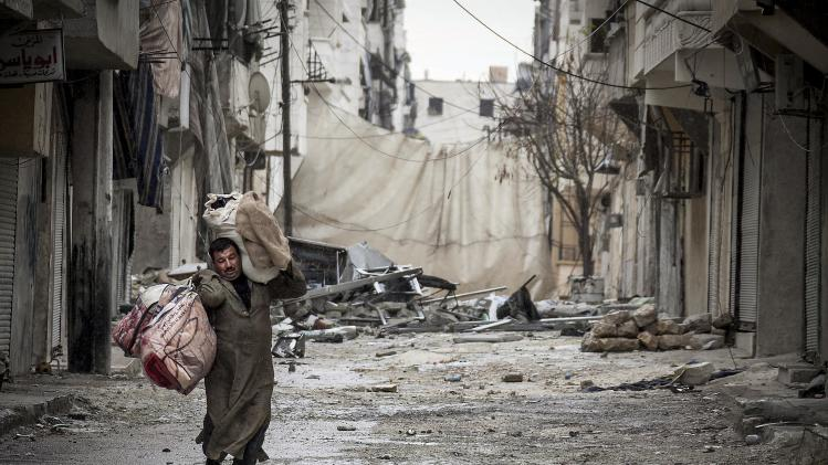 In this Tuesday, Dec. 11, 2012 photo, a Syrian man carries his belongings after his home was damaged due to fighting between Free Syrian Army fighters and government forces in Aleppo, Syria. (AP Photo/Narciso Contreras)
