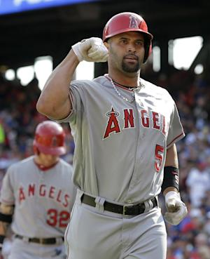 Los Angeles Angels' Albert Pujols (5) celebrates his solo home run off of Texas Rangers' Jason Frasor as the Angels' Josh Hamilton (32) stands at the plate in the sixth inning of a baseball game Saturday, April 6, 2013, in Arlington, Texas. Pujols homered twice to offset another tough day for Hamilton in his second game back in Texas, and the Angels beat the Rangers 8-4 Saturday. (AP Photo/Tony Gutierrez)