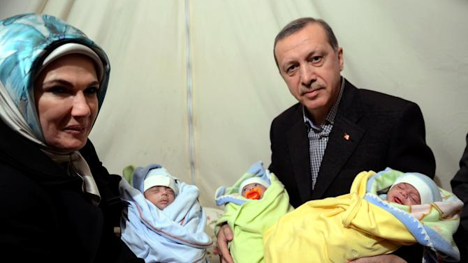 In this photo provided by Turkish Prime Minister's Press Service, Turkish Prime Minister Recep Tayyip Erdogan, and his wife Emine Erdogan hold newly born babies during a visit to a Syrian refugee camp in Sanliurfa, Turkey, Sunday, Dec. 30, 2012. Erdogan repeated a call on Syrian President Bashar Assad to step down. (AP Photo/Kayhan Ozer)