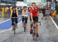 Marussia Formula One driver Max Chilton (R) of Britain rides his bicycle at the Sepang International Circuit, ahead of the Malaysian F1 Grand Prix March 21, 2012. Chilton is one of five Formula One rookies among the 22 drivers on the grid this season and while the Briton is still learning the art of being lapped he is confident he can make an impact. Chilton was promoted from Marussia's GP2 team after coming fourth in that series last year and despite finishing a lowly 17th at the season-opener in Australia, the 21-year-old believes he is at the start of a long journey at the sport's elite level. REUTERS/Edgar Su (MALAYSIA  - Tags: SPORT MOTORSPORT F1)