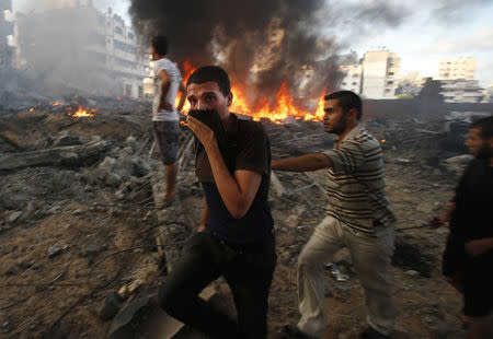 Palestinians walk past a fire following what witnesses said was an Israeli air strike on a building in Gaza City