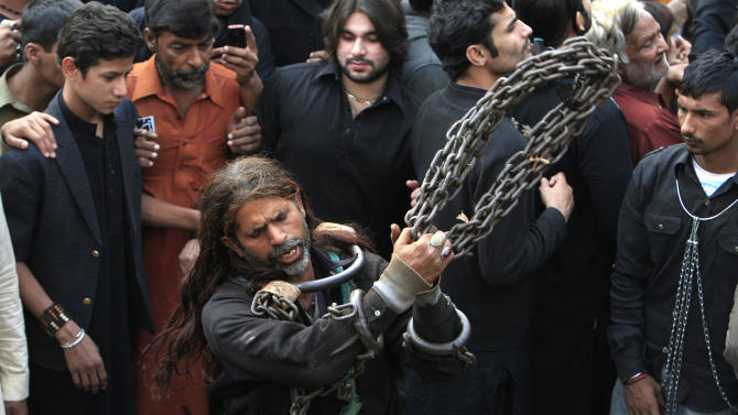 A Pakistani Shiite Muslim flagellates himself with chains during a Muharram procession in Lahore, Pakistan on Saturday, Nov. 24, 2012. Muharram is a month of mourning in remembrance of the martyrdom of Imam Hussein, the grandson of Prophet Mohammed. (AP Photo/K.M. Chaudary)