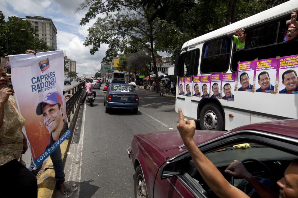 Supporters of Venezuela's President Hugo Chavez chant pro government slogans at supporters of the opposition's presidential candidate Henrique Capriles, left, as the Chavistas caravan through the streets of Caracas, Venezuela, Friday, Sept. 28, 2012. Venezuela's presidential election is scheduled for Oct. 7. (AP Photo/Rodrigo Abd)