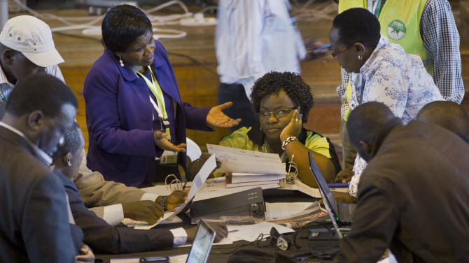 Official representatives of the various political parties and electoral workers discuss while reviewing newly received results, at the National Tallying Center in Nairobi, Kenya Wednesday, March 6, 2013. Election officials in Kenya are counting by hand the ballots from the nation's presidential election after abandoning the electronic tabulation system which has posted early returns. (AP Photo/Ben Curtis)