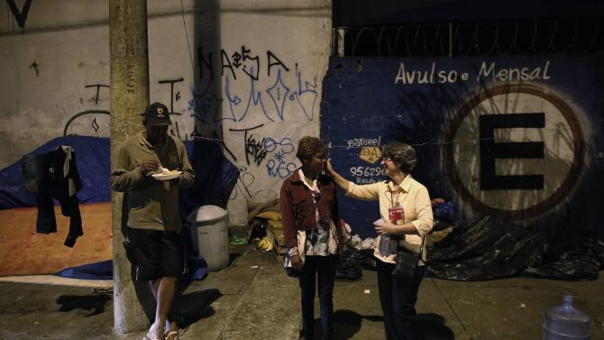 Sonia, a member of Sao Miguel Arcanjo church, greets a homeless woman as her friend eats on a street during a free Christmas dinner in Sao Paulo