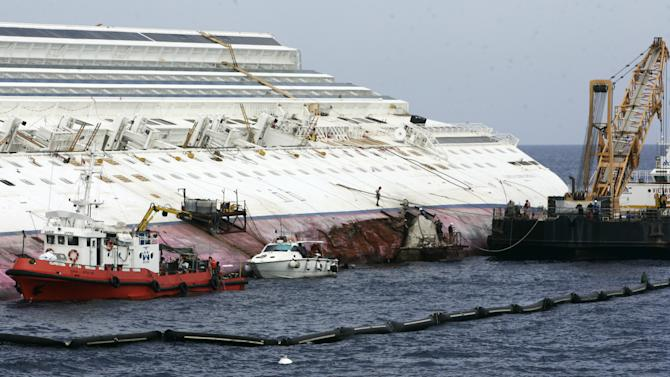 """Workers begin to remove the tons of rocky reef embedded into the Costa Concordia cruise ship's hull, a first step in plans to eventually tow the wreck away from the Giglio Island, Italy, where it ran aground last January, Thursday, July 12, 2012. The whole removal process could take as long as a year. In a broadcast interview Tuesday, Concordia's captain Francesco Schettino described the collision as a """"banal accident"""" in which """"destiny"""" played a role. (AP Photo/Gregorio Borgia)"""