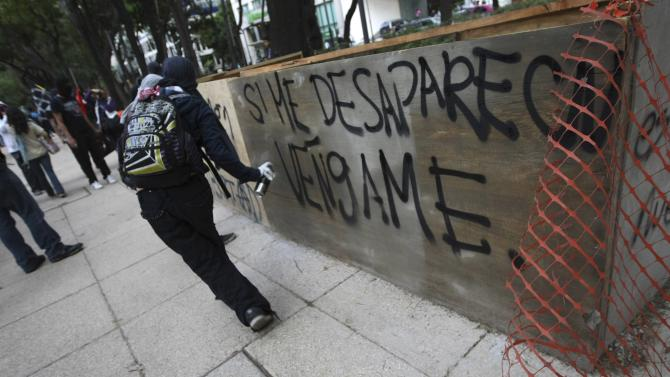 An activist sprays graffiti during a march to demand justice for the 43 missing students from Ayotzinapa Teacher Training in Mexico City