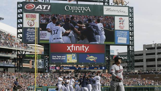 Minnesota Twins' Oswaldo Arcia walks off the field as the Detroit Tigers celebrate their American League Central division during a baseball game in Detroit, Sunday, Sept. 28, 2014. (AP Photo/Carlos Osorio)