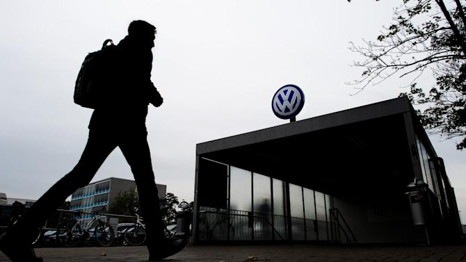 A VW employee enters the Volkswagen factory site through Gate 17 in Wolfsburg, Germany, Oct. 6, 2015. For Volkswagen, the cost of its cheating on emissions tests in the U.S. is likely to run into the tens of billions of dollars and prematurely end its long-sought status as the world's biggest carmaker.  (Julian Stratenschulte/dpa via AP)