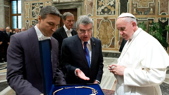 "In this photo provided by the Vatican newspaper L'Osservatore Romano Pope Francis is presented a gift by Thomas Bach, president of the International Olympic Committee, in the Clementine hall at the Vatican Saturday, Nov. 23, 2013. Francis told several hundred members of the European Olympic Committees that when sport ""is considered only in economic terms and consequently for victory at every cost ... it risks reducing athletes to mere trading material from whom profits are extracted."" The pope added that ""sport is harmony but if money and success prevail as the aim this harmony crumbles."" (AP Photo/L' Osservatore Romano, ho)"