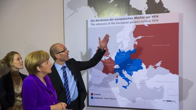 FILE - In this May 28, 2014 file photo, curator Andreas Mix, right, explains a map of alliances of the European powers prior to World War I to German Chancellor Angela Merkel, second left, during a World War I exhibition at the Historical Museum in Berlin. More than 65 million men were mobilized to fight in World War I, including grandfathers and relatives of many of today's heads of state and government. On Thursday, June 26, 2014, in the Belgian city of Ypres near the blood-drenched battlefields of Flanders, leaders of the 28 member states of the European Union will gather to mark the 100th anniversary of the beginning of the conflict that wreaked great death and destruction on their continent. (AP Photo/Thomas Peter, Pool)