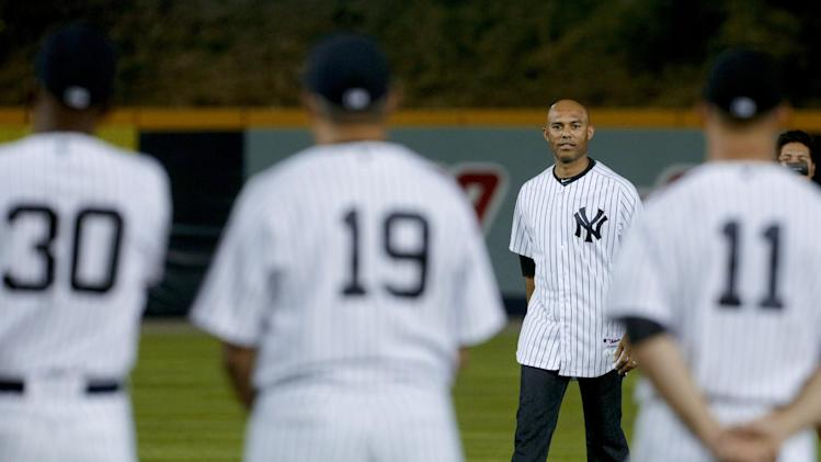 Retired New York Yankees relief pitcher Mariano Rivera walks front of Yankees player David Robertson (30), Luis Sojo (19) and Brett Gardner (11) at an exhibition game between the Yankees and the Maimi Marlins, at Rod Carew Stadium in Panama City, Saturday, March 15, 2014. (AP Photo/Arnulfo Franco)