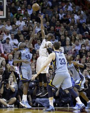 Miami Heat's Dwyane Wade (3) shoots over Memphis Grizzlies' Zach Randolph (50) in the second half of an NBA basketball game in Miami, Friday, March 1, 2013. The Heat won 98-91. (AP Photo/Alan Diaz)
