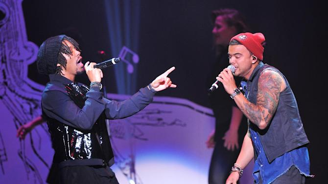 """Singers Lupe Fiasco, left, and Guy Sebastian perform at """"Play It Forward: A Celebration of Music's Evolution and Influencers"""" at the Grammy Foundation's 15th Annual Music Preservation Project, Thursday, Feb. 7, 2013, in Los Angeles. (Photo by Vince Bucci/Invision/AP)"""