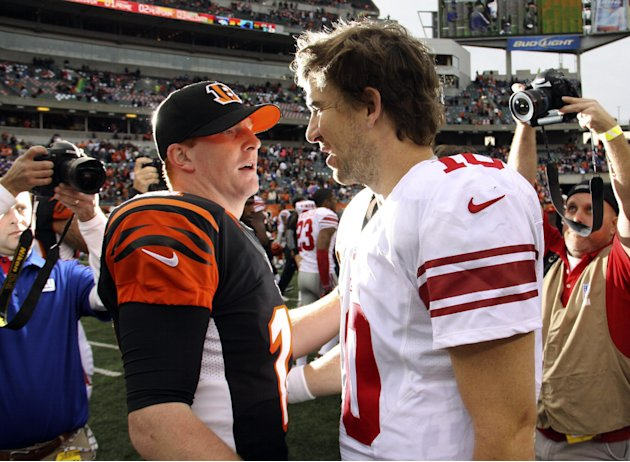 Cincinnati Bengals quarterback Andy Dalton (14) meets with New York Giants quarterback Eli Manning (10) after the Bengals' 31-13 win in an NFL football game, Sunday, Nov. 11, 2012, in Cincinnati. (AP 