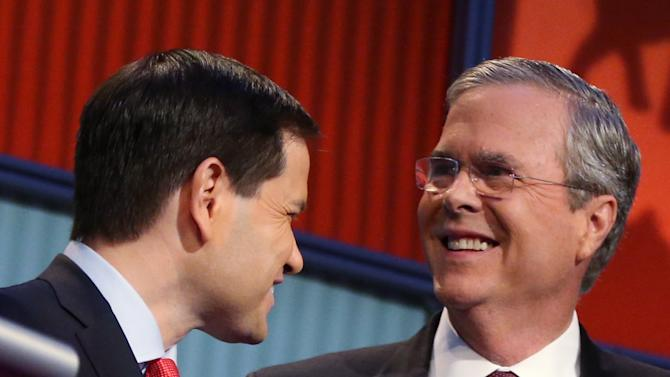FILE - In this Aug. 6, 2015 file photo, Republican presidential candidates Marco Rubio, left, and Jeb Bush talk during a break during the first Republican presidential debate at the Quicken Loans Arena in Cleveland. There are more than a dozen major candidates in the Republican presidential primary, and while outsiders Donald Trump and Ben Carson top the current preference polls, it's the two Floridians, Bush and Rubio, at the head of the second wave.  (AP Photo/Andrew Harnik)