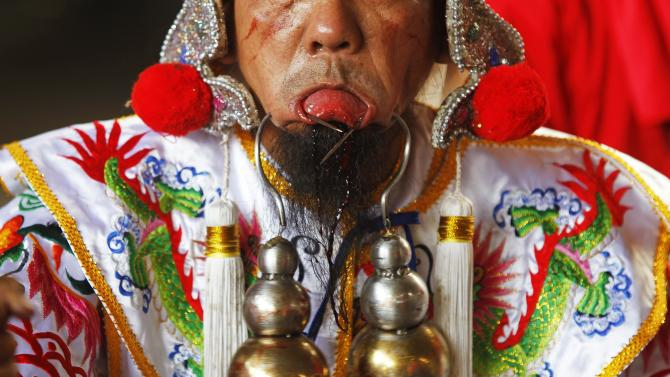 A worshipper, with steel hooks pierced through his cheeks, takes part in Hei Neak Ta, or Spirit Parade, which marks the end of Chinese New Year celebrations, in Phnom Penh