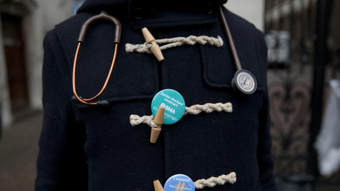 A junior doctor wears badges and a stethoscope on his coat, as he takes part in a 24-hour strike on a picket line outside St Mary's Hospital, which includes the private wing where the two royal babies were born in recent years, in London, Wednesday, Feb. 10, 2016. Thousands of junior doctors have walked off the job in England in a dispute over pay and working conditions. (AP Photo/Matt Dunham)