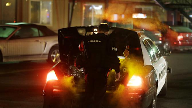 A Tukwila Police officer puts gear in his trunk after returning to his car near the scene of an overnight shooting that left five people dead, Monday, April 22, 2013, at an apartment complex in Federal Way, Wash. (AP Photo/Ted S. Warren)