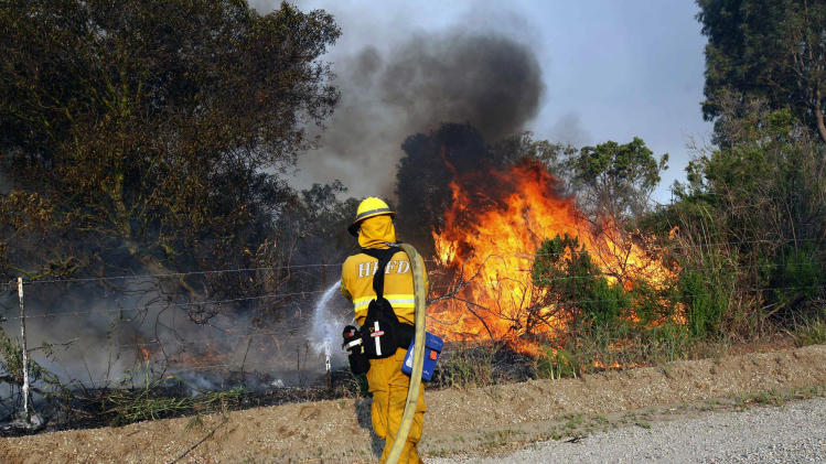 A firefighter from Huntington beach works to extinguish a brush at Point Mugu Friday, May 3, 2013. A Southern California wildfire carving a path to the sea grew to more than 15 square miles and crews prepared Friday for another bad day of gusting winds and searing weather. (AP Photo/Nick Ut)