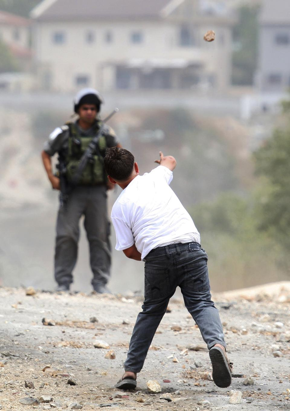A Palestinian youth throws a stone at an Israeli border policeman during clashes with Israeli troops after the weekly protest against the expansion of the nearby Jewish settlement of Kdumim, in the northern West Bank village of Kufr Qaddum, Friday, June 22, 2012. (AP Photo/Nasser Ishtayeh)