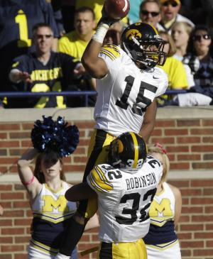 Iowa wide receiver Derrell Johnson-Koulianos (15) is lifted by teammate running back Adam Robinson (32) after scoring a touchdown during the second quarter of an NCAA college football game against Michigan in Ann Arbor, Mich., Saturday, Oct. 16, 2010. (AP Photo/Carlos Osorio)