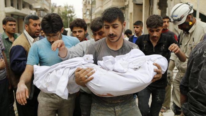 A man carries a dead body in Aleppo's Karam al-Beik neighborhood