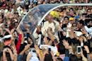 Pope Francis waves to the crowd as he arrives to celebrate mass at Nu Guazu field on the outskirts of Asuncion, Paraguay on July 12, 2015