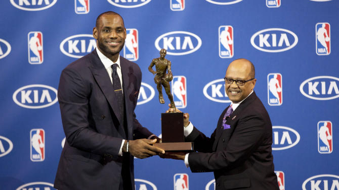 Miami Heat's LeBron James, left, and Kia Motors' Percy Vaughn pose for photos during an NBA basketball news conference, Sunday, May, 5, 2013, in Miami. James was formally announced as having won his fourth Most Valuable Player award Sunday. (AP Photo/J Pat Carter)