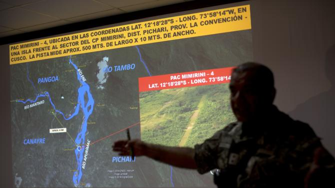 In this Sept. 19, 2014 photo, a counternarcotics officer explains to the press the two weeks campaign to eradicate clandestine airstrips at the Mazamari counternarcotics military base in the Apurimac, Ene and Mantaro River Valleys, or VRAEM, the world's No. 1 coca-growing region, in Junin, Peru. The dynamiting of craters by Peruvian security forces into clandestine airstrips in the VRAEM cuts into profits but hardly discourages cocaine traffickers who net tens of thousands of dollars with each flight. (AP Photo/Rodrigo Abd)