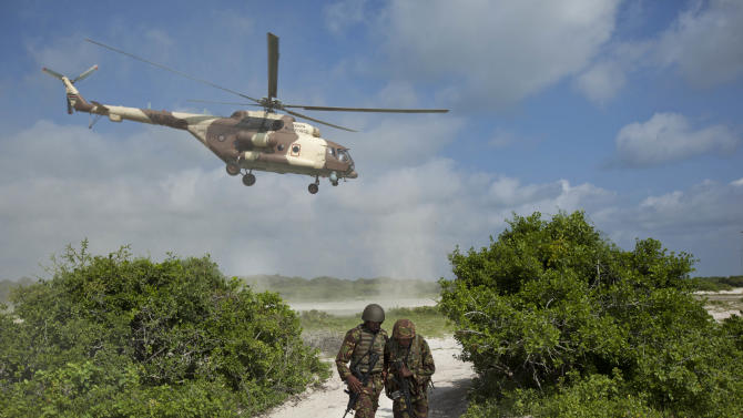 FILE - In this Wednesday, Dec. 14, 2011 file photo, two Kenyan army soldiers shield themselves from the downdraft of a Kenyan air force helicopter as it flies away from their base near the seaside town of Bur Garbo, Somalia. Kenya's military said Friday, Sept. 28, 2012 that its troops attacked Kismayo, the last remaining port city held by al-Qaida-linked al-Shabab insurgents in Somalia, during an overnight attack involving a beach landing. (AP Photo/Ben Curtis, File)